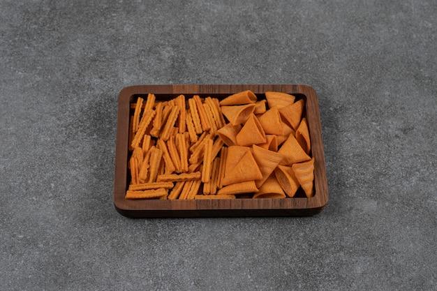 Een dienblad met maïsspaanders en gedroogd brood op het marmeren oppervlak