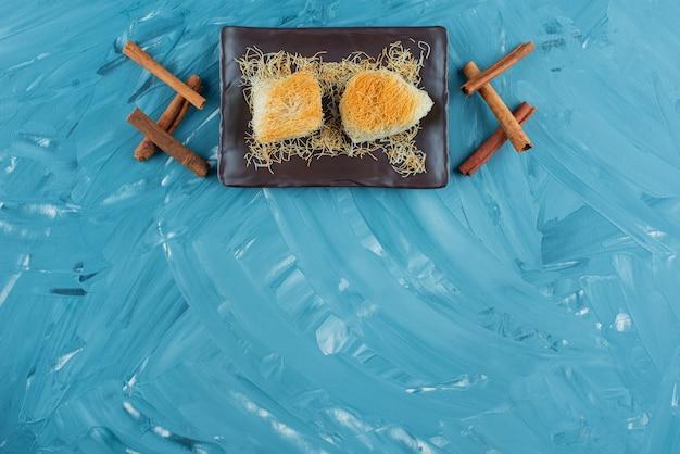 Een dienblad met turkse lekkernijen met pijpjes kaneel op een blauwe achtergrond.