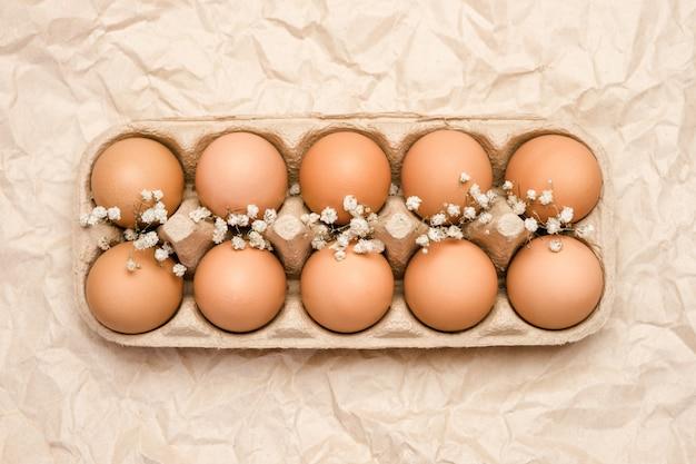 Een dienblad van bruine verse kippeneieren op gerimpeld kraftpapier. milieuvriendelijke eierproductie.