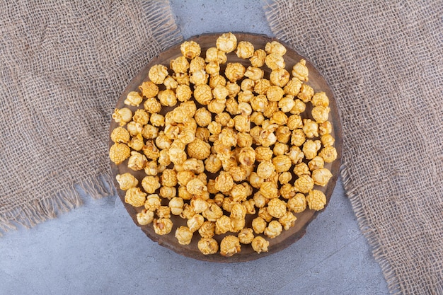 Een dienblad vol popcornsnoepjes en twee stukken stof op een marmeren ondergrond