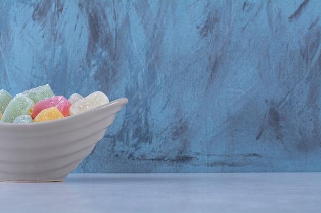 Een diep bord vol kleurrijke, suikerachtige fruitmarmelades
