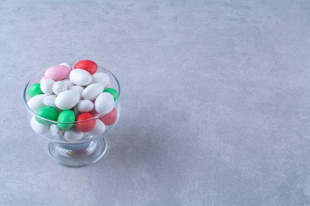 Een diepe glazen plaat vol kleurrijke bonen snoepjes op grijze tafel.
