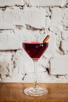 Een dieprode cocktail in een nick & nora glas gegarneerd met kaneel
