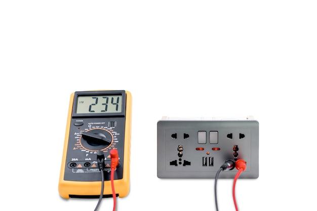 Een digitale meter gebruiken om de spanning te meten op een stopcontactdoos geïsoleerd op een witte achtergrond.