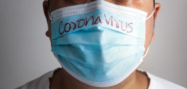 Een dikke aziatische man met een blauw masker schrijft het woord coronavirus. concept preventie van covid-19 sociale afstand voorkomt de verspreiding van het virus en zorgt voor zwaarlijvige mensen.