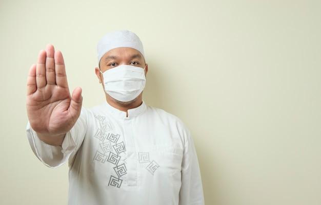 Een dikke aziatische moslimman die met de hand een masker draagt dat een stopgebaar symboliseert