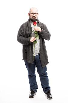 Een dikke kale man met een bril en een baard houdt een rode roos in zijn handen. geïsoleerd via witte muur. verticaal.