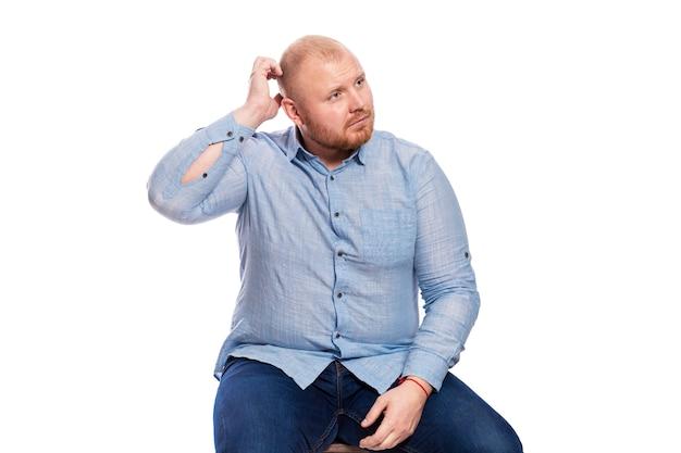 Een dikke roodharige man met een baard in een blauw shirt en een spijkerbroek zit op zijn hoofd en krabt. geïsoleerd.
