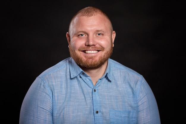 Een dikke roodharige man met een baard in een blauw shirt