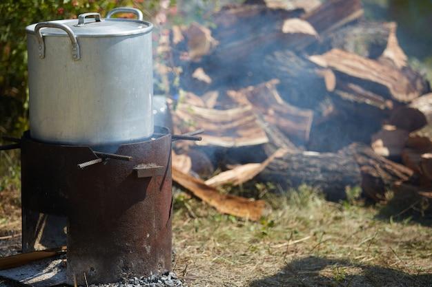 Een diner wordt in grote pan voorbereid voor een groot gezelschap in de natuur