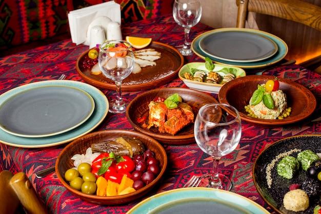 Een dineropstelling met salade van bijgerechten en augurkenplaten