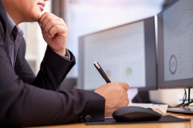 Een discrete zakenman denkt na en kijkt naar de computer op het werk
