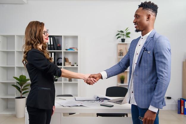 Een diverse aantrekkelijke man en vrouw business team handdruk op kantoorgebouw