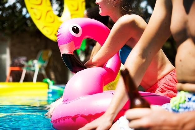 Een diverse groep vrienden die van de zomertijd genieten bij het zwembad met opblaasbare dobbers