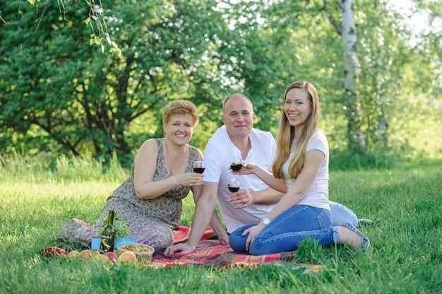 Een dochter met haar oude ouders drinkt vrolijk samen wijn en breekt een bril. spreek toast uit. het huwelijksverjaardag van ouders wordt gevierd.