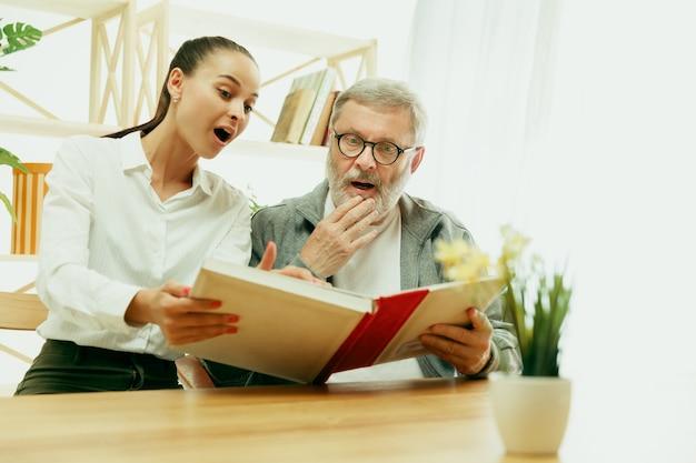 Een dochter of kleindochter brengt tijd door met de grootvader of senior man. familie- of vaderdag, emoties en geluk. lifestyle portret thuis. meisje dat voor papa zorgt. een boek lezen.