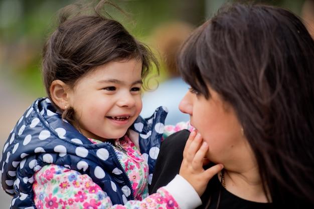 Een dochtertje in de armen van haar moeder kijkt haar aan en lacht