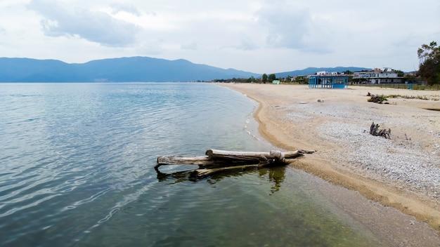 Een dode boomstam op een strand, egeïsche zeekust, gebouwen en heuvels, asprovalta, griekenland