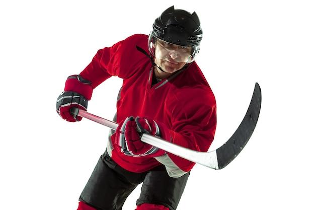 Een doelpunt maken. mannelijke hockeyspeler met de stok op ijsbaan en witte muur. sportman uitrusting dragen en helm oefenen. concept van sport, gezonde levensstijl, beweging, beweging, actie.