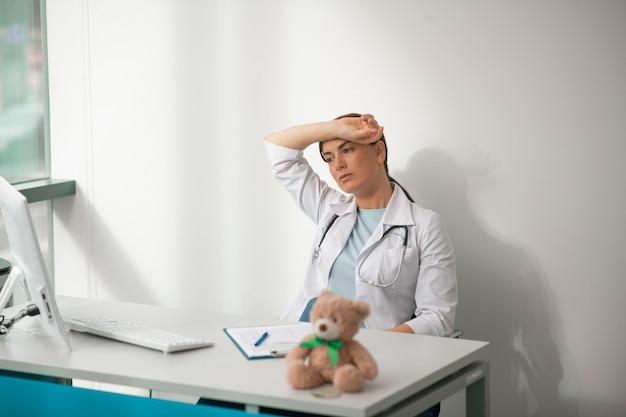 Een dokter die aan tafel zit en zich moe voelt
