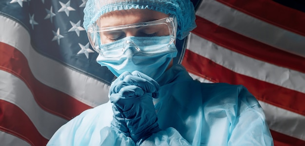 Een dokter die moe is na een zware dag, bidt tegen de achtergrond van de amerikaanse vlag