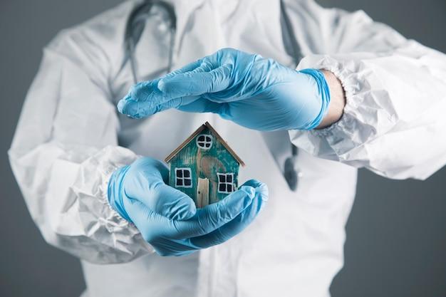 Een dokter in een wit beschermend uniform beschermt een klein huis op een grijs tafereel