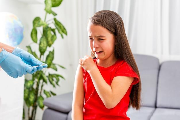 Een dokter injecteert een vaccin bij een klein meisje. het meisje is bang en huilt.