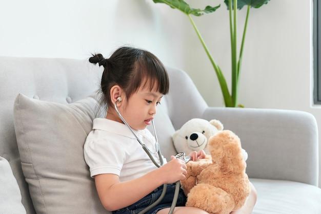 Een dokter meisje spelen en genezen beer op de pediatrie