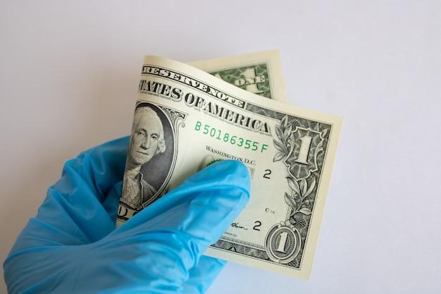 Een dollarbiljet opgerold in de hand in medische handschoen op witte achtergrond