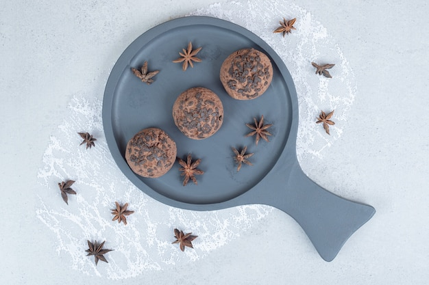 Een donker bord met chocoladekoekjes met steranijs