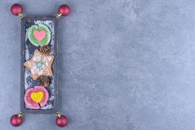 Een donker bord met koekjesster en suikerachtige geleisuikergoed
