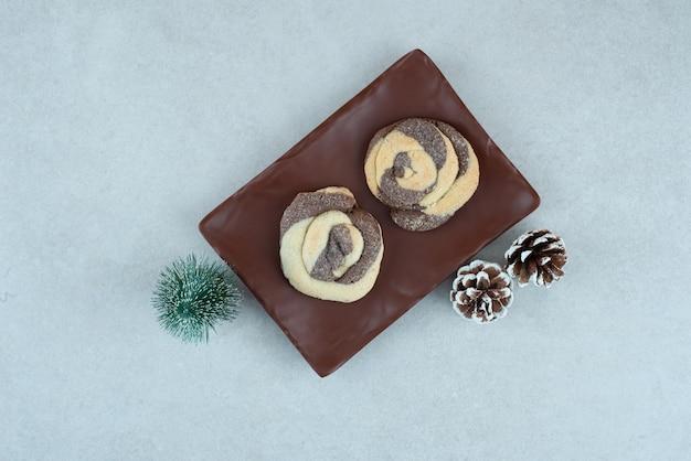 Een donker bord met twee heerlijke koekjes met dennenappels en kerstboom.