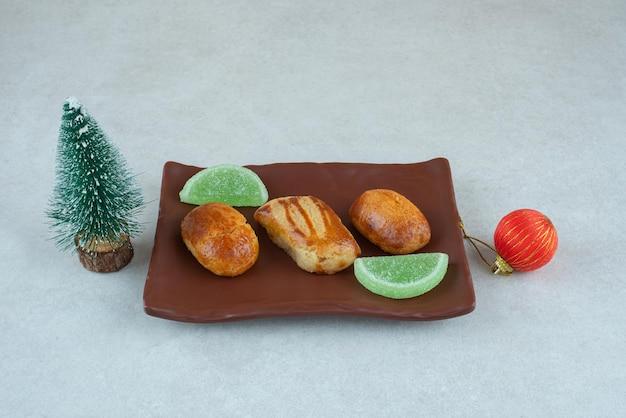 Een donker bord met zoete gebakjes met marmelade en kerstspeelgoed.