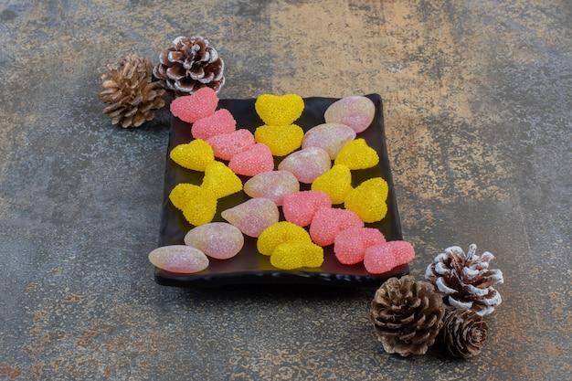 Een donker bord vol hartvormige geleisuikergoed met dennenappels. hoge kwaliteit foto