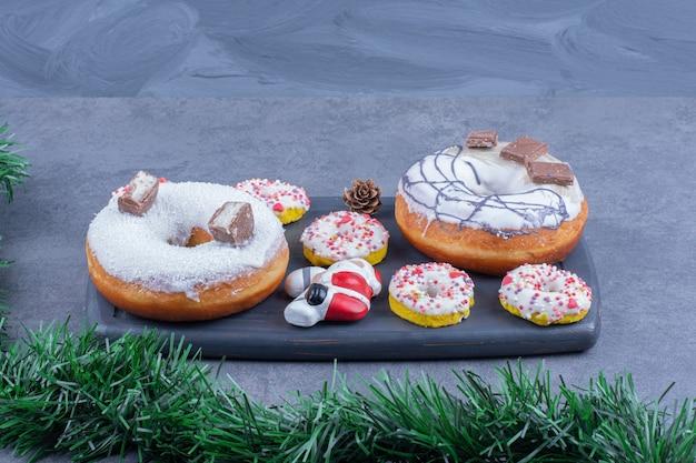 Een donker bord vol taarten met suikerpoeder