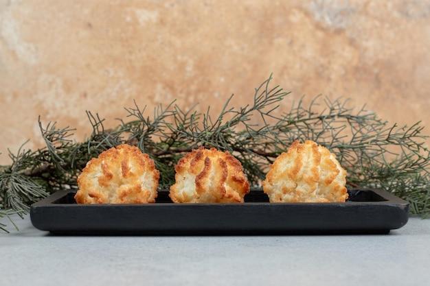 Een donker bord vol zoete, frisse ronde koekjes.