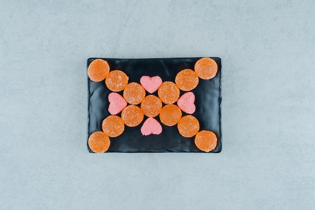 Een donker bord vol zoete sinaasappel gelei snoepjes met roze hartvormige gele snoepjes