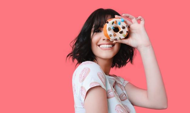 Een donkerbruin jong meisje dat u door een smakelijke doughnut bekijkt glimlacht en adverteert iets op een koraalachtergrond
