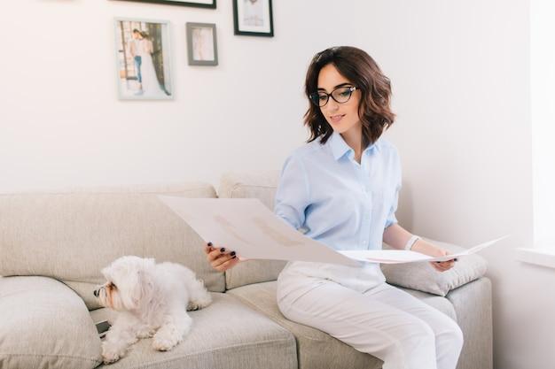 Een donkerbruin jong meisje zit op de bank in de studio. ze draagt een blauw shirt en een witte broek. ze kijkt naar de schetsen die ze in haar beide handen heeft.