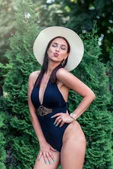 Een donkerbruine vrouw in een hoed en zwempak rond de zomergreens