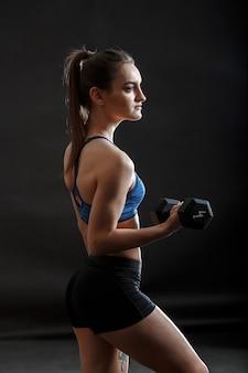 Een donkerbruine vrouw in sportkleding staat met dumbells in haar handen