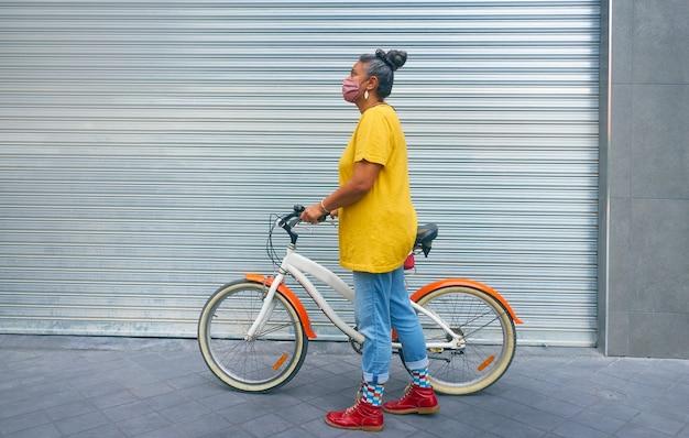 Een donkerbruine vrouw met grijs haar en een masker die een fiets vasthoudt voor een ritje door de stad.
