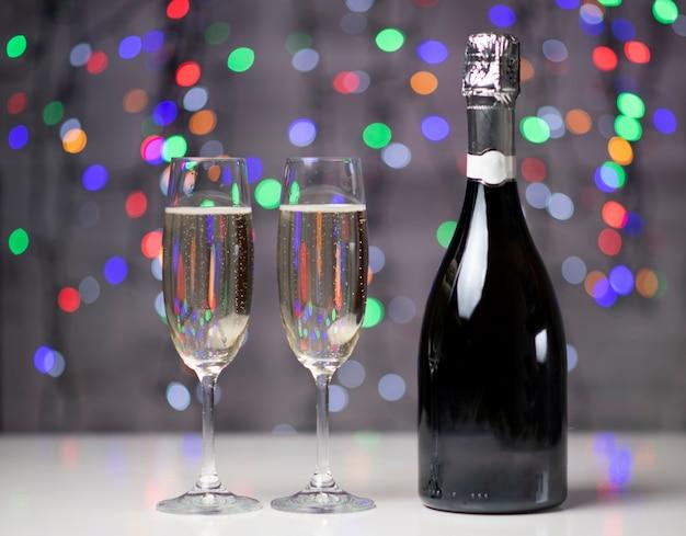 Een donkere fles wijn op een mooie feestelijke bokeh steekt aan