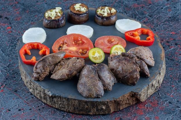 Een donkere houten plank van groenten en vlees.