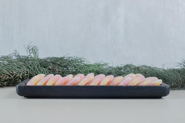 Een donkere houten plank vol hartvormige jelly snoepjes.
