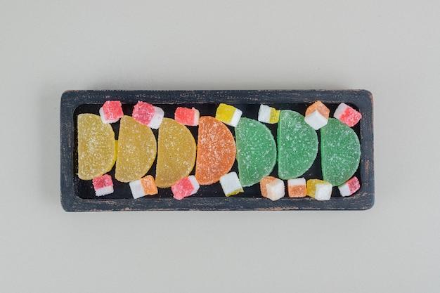 Een donkere houten plank vol kleurrijke, suikerachtige marmelades.
