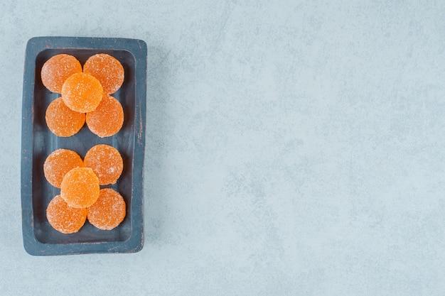 Een donkere houten plank vol zoete sinaasappelgeleisuikergoed op een witte ondergrond