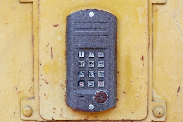 Een donkere intercom met ronde knoppen en een draaiknop op een metalen deur.