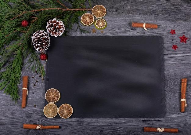 Een donkere kaasschotel met kerstdecor en kopie ruimte voor tekst
