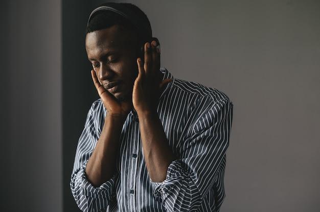 Een donkere man op een grijze achtergrond luistert naar muziek en geniet van prachtige lyrische muziek. hoge kwaliteit foto